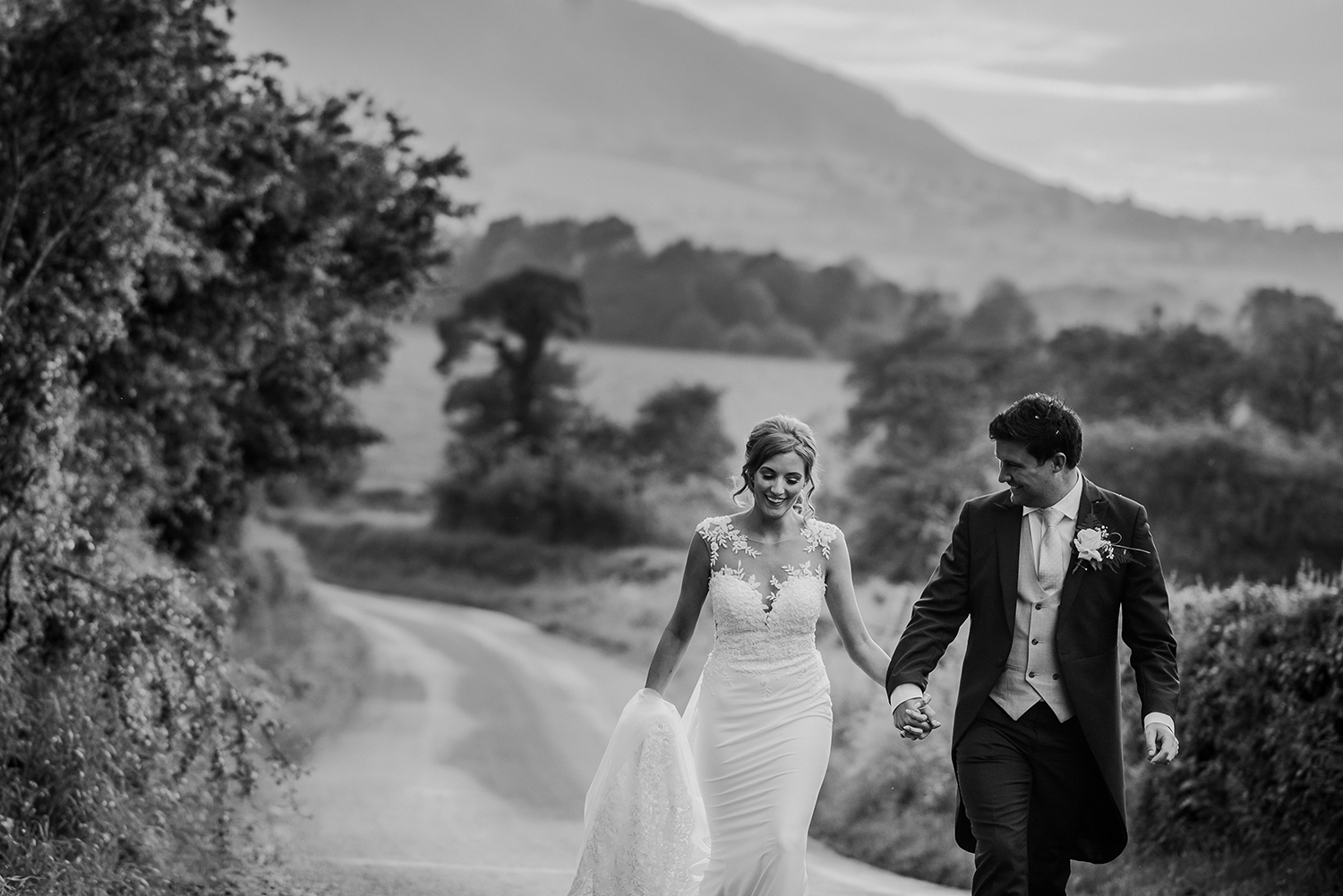 bw photo of bride and groom walking up the path