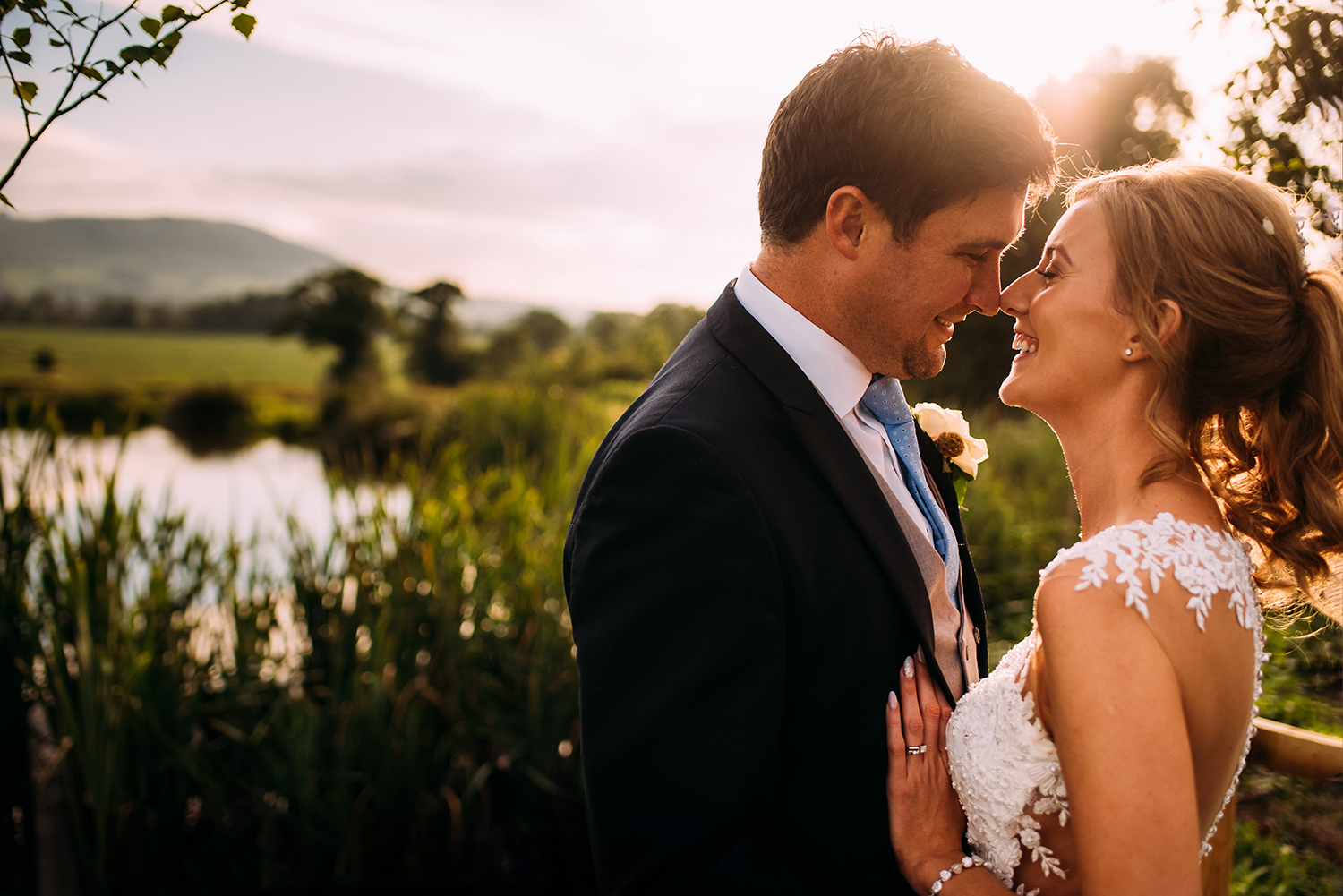 bride and groom in golden light by the water at Bashall Barn