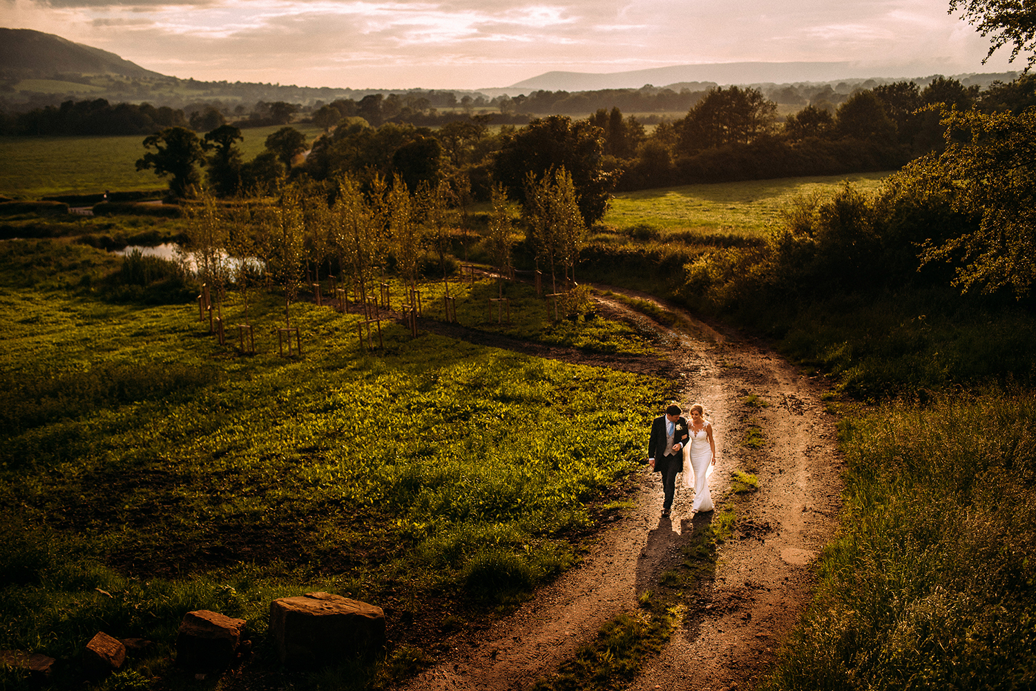 elevated wide shot of bride and groom walking through stunning scenery in the valley