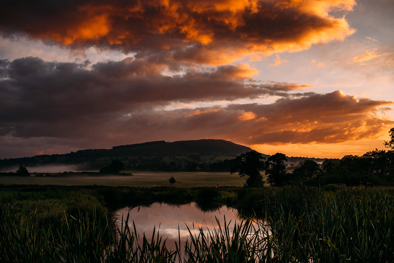 sun sets over the water and hills