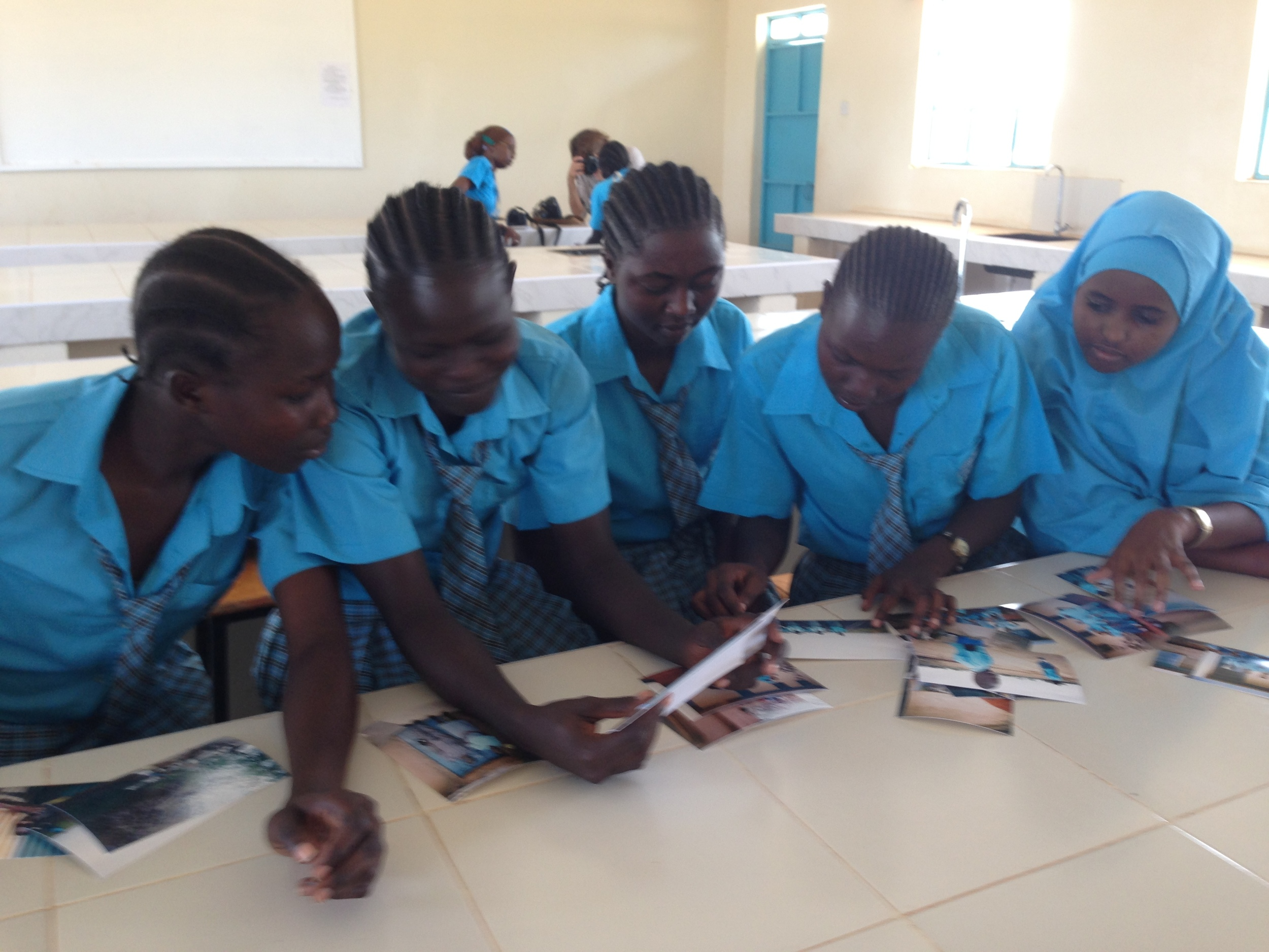 Rita, Nhial, Zahira, Nyimuch and Fardosa looking at the polaroid photos they took.