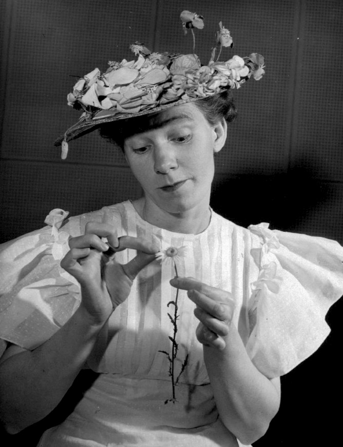 Photo of Minnie Pearl wondering if her latest male interest loves her or not. Grand Ole Opry, 1949. Wikimedia Commons
