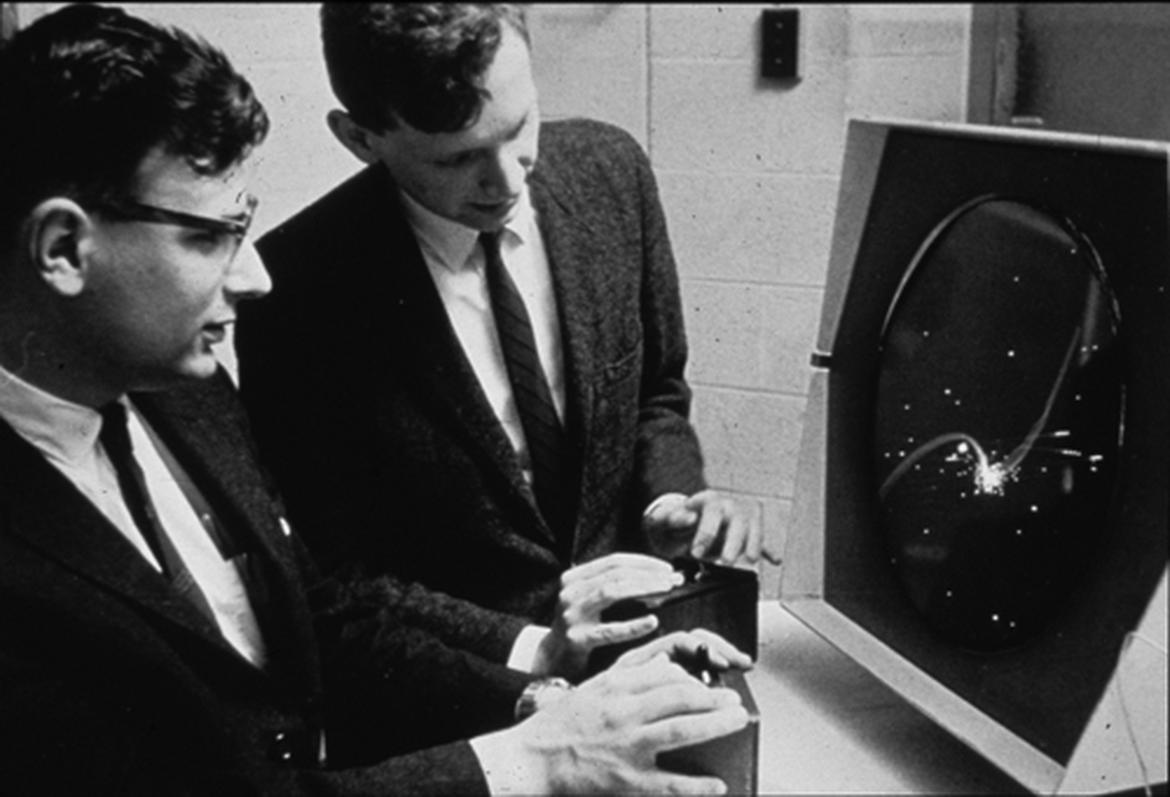 In this archival shot, we see Dan Edwards on the left and Peter Samson playing Spacewar on the PDP-1 display.