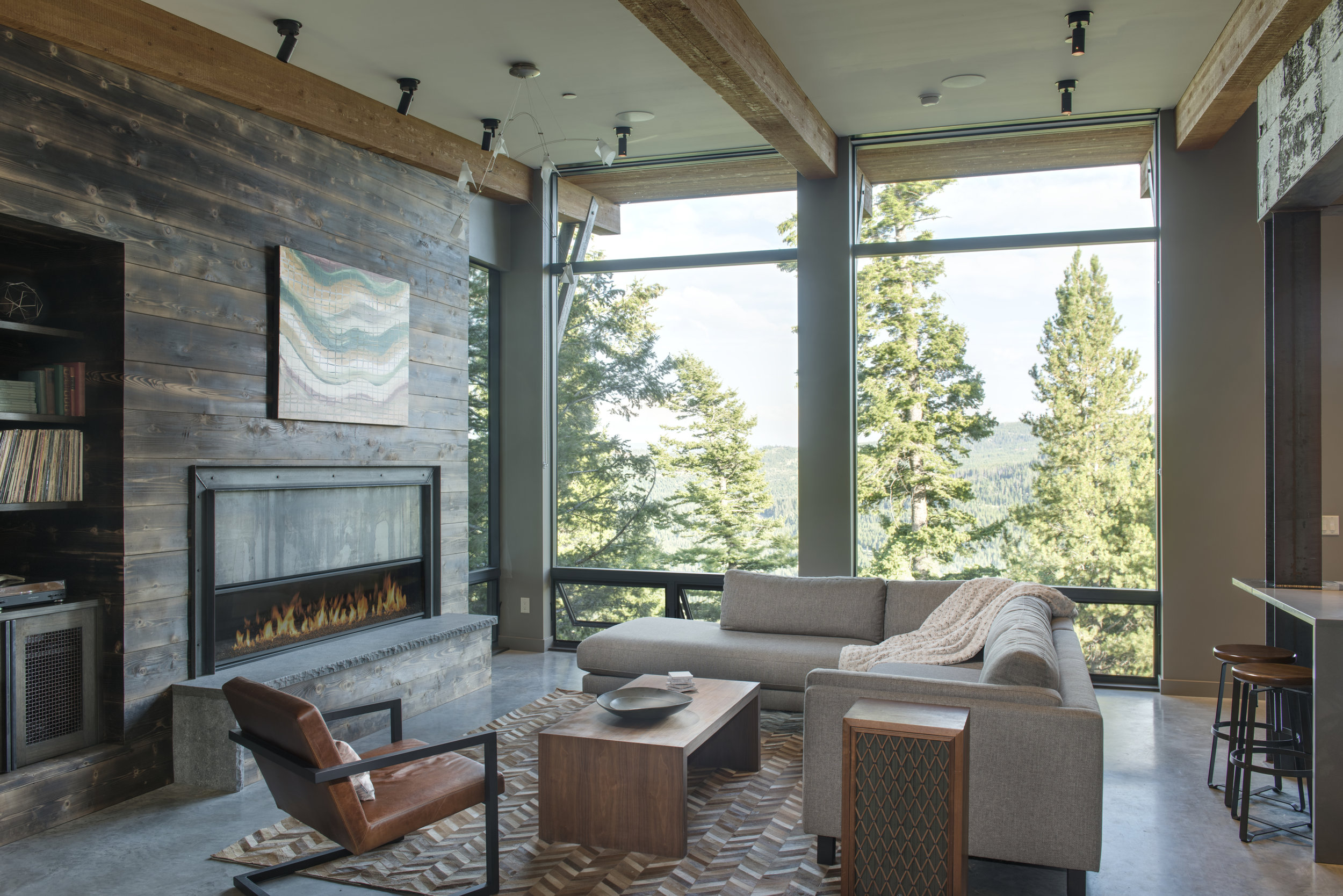 This amazing  Reid Smith Architects  designed home is located on a bluff in  Spanish Peaks Mountain Club . The burned wood wall, the windows, and the birch bark wallpaper put this great room as one of my absolute favorites!!