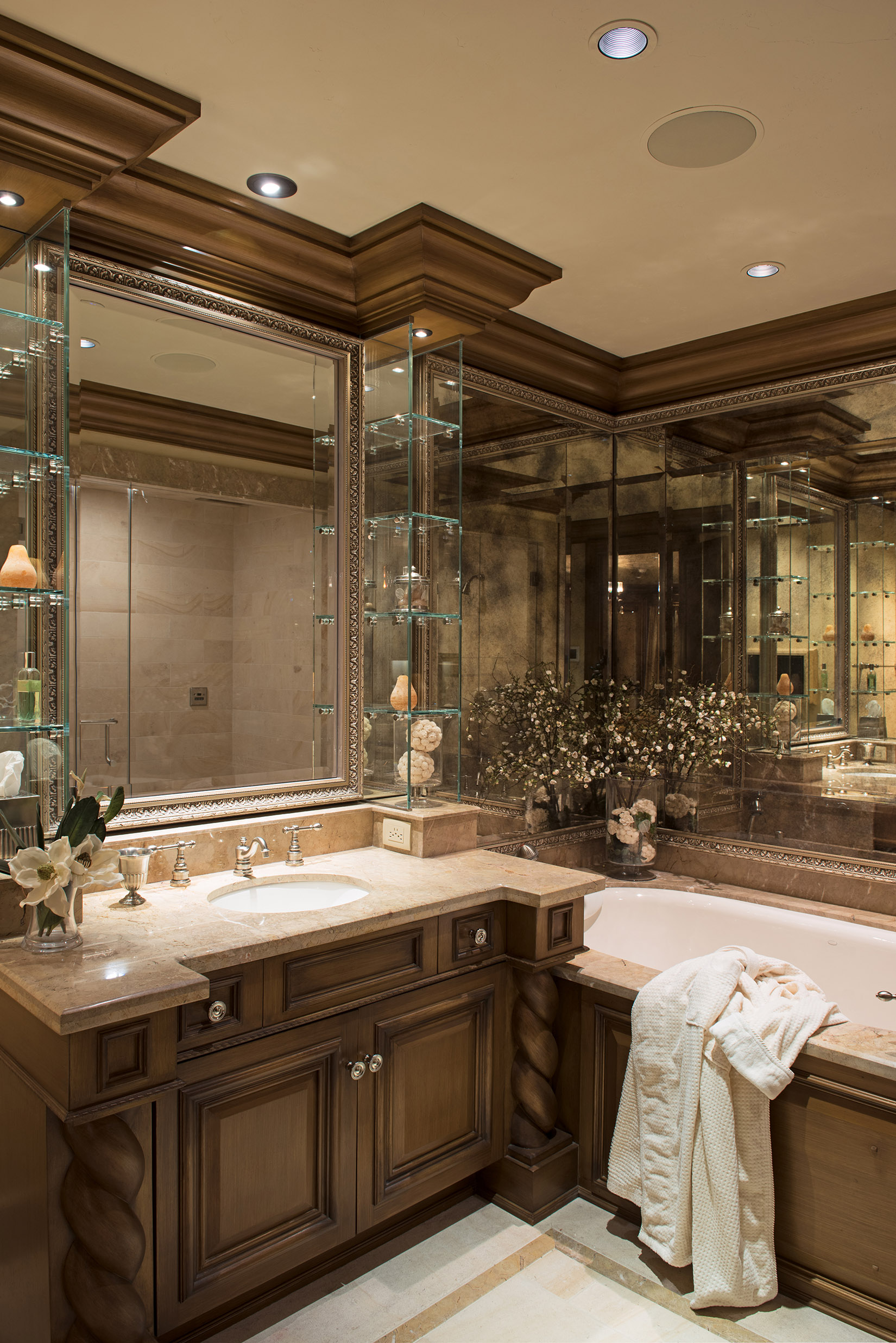 This junior guest suite bathroom is stunning with the mirrors, custom vanity, and glass shelving.