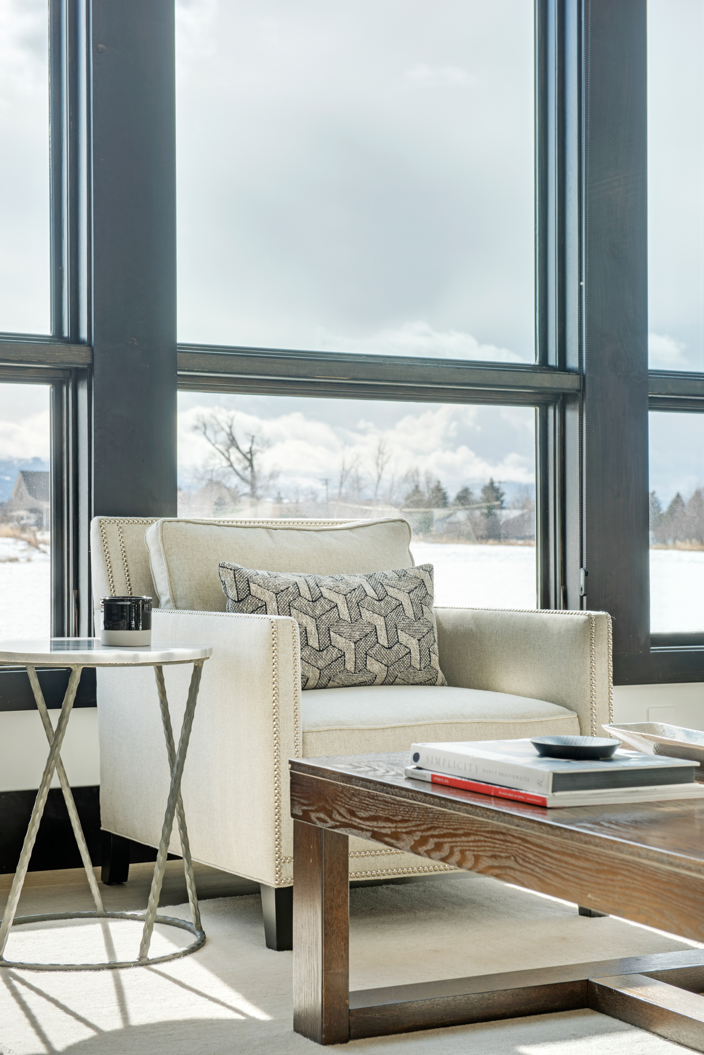 The great room has amazing views and the contemporary look of the windows is complimented with the stylish furnishings. I love the geometric patten on the pillow!