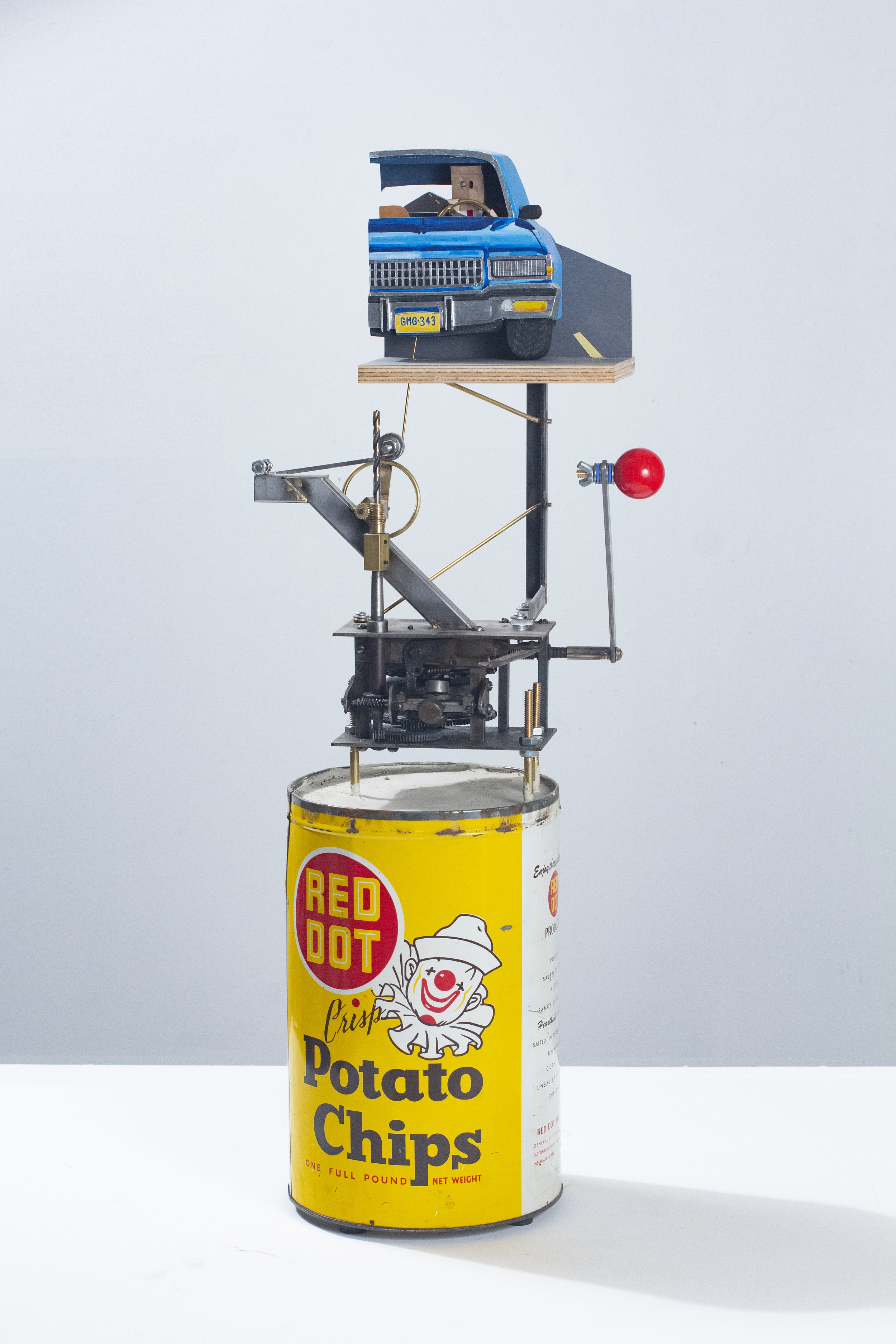 """""""Executive Toy: the lonely road"""" 11.5x28.5x7 inches Concrete, vintage tin, steel, brass, arcade game joystick, plywood, hardware, sandpaper, flashe, silica bronze, paper bag, skateboard bearing, denim, paper, cotton and phonograph motor"""