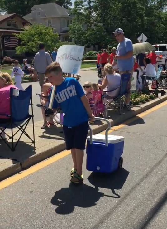 10 year old selling water out of a cooler with a sign