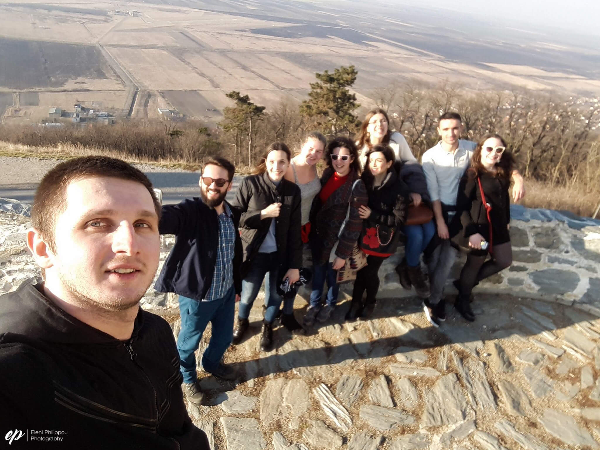 Happy faces trying to catch their breath upon reaching the top of the hill at the tower, overlooking the whole city. The fields behind border Romania.