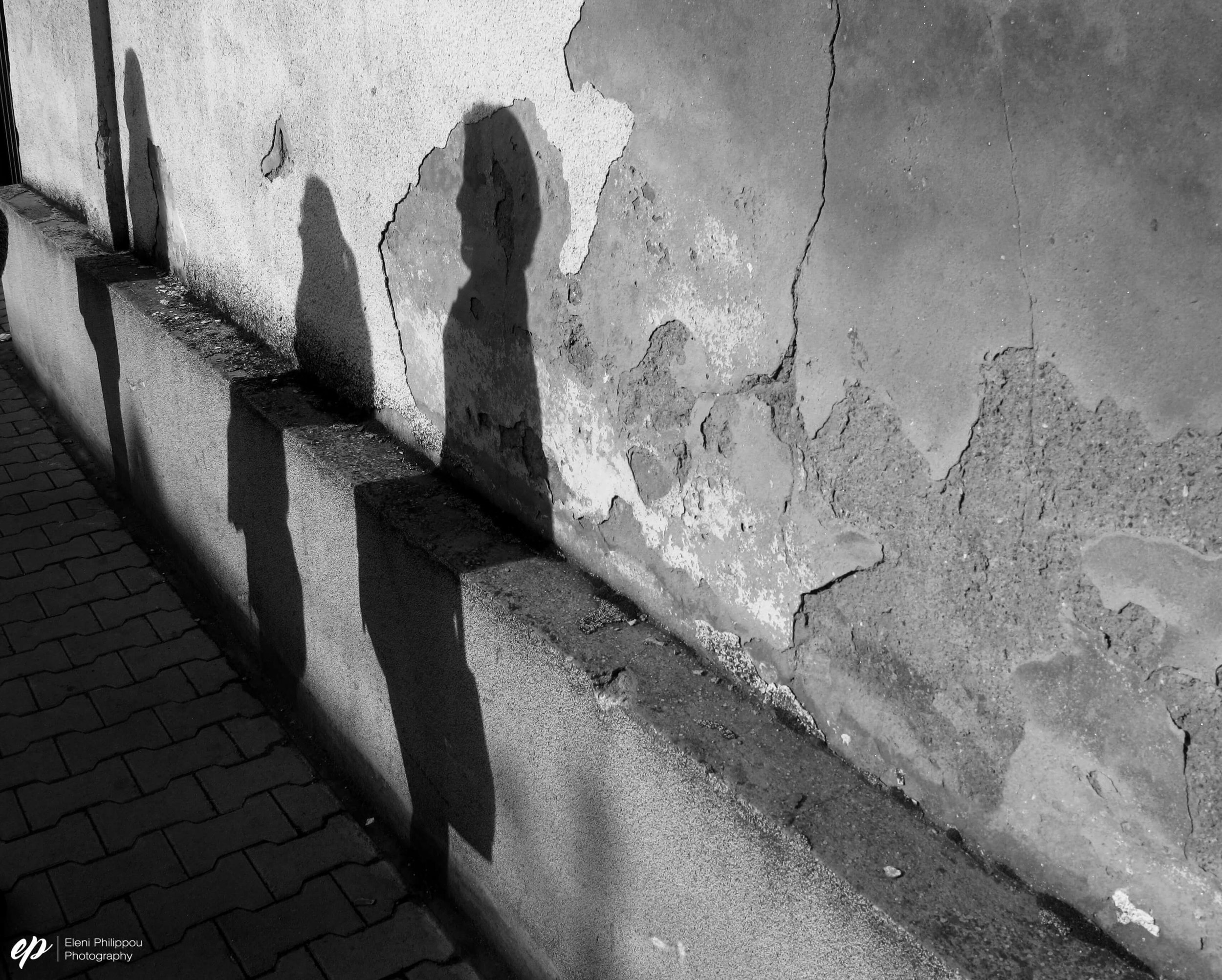 Figures sit on an old wall during an afternoon walk dissecting neighbourhoods.