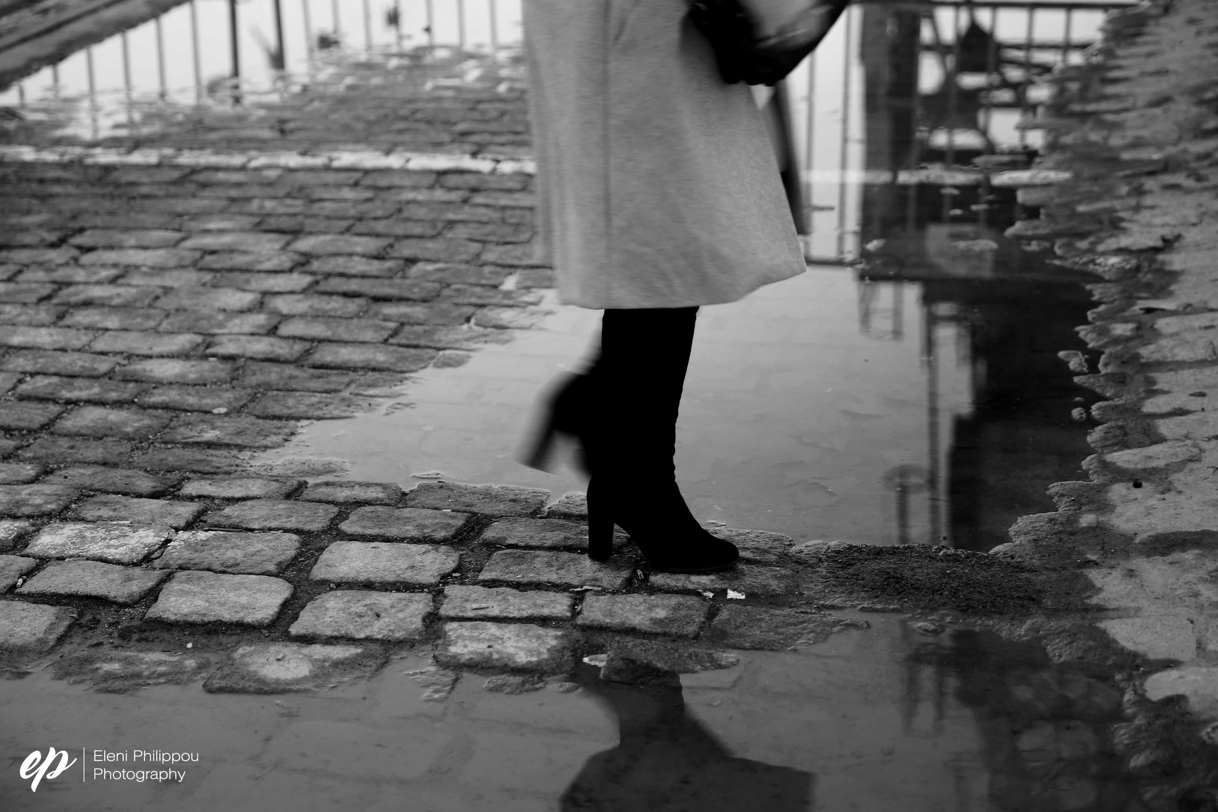 woman passes over a rain puddle in Thessaloniki, Greece