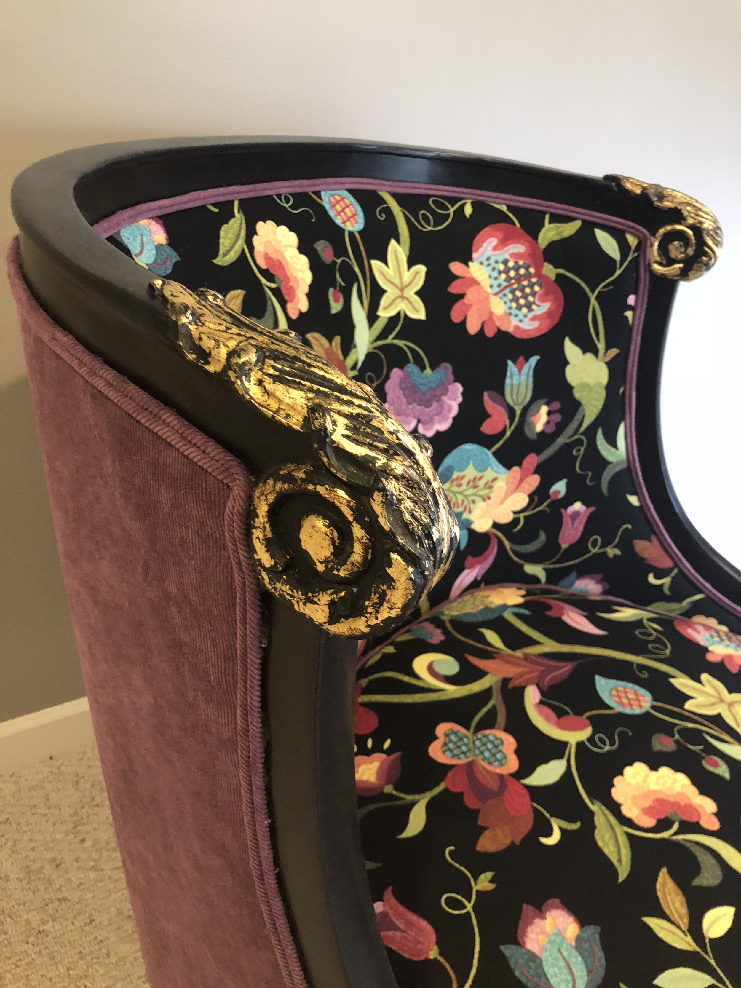 Upholstered in a solid fabric on the back with a print on the inside.  The solid fabric was also used as the piping for the entire piece.  We finished the wood in black and added gold leaf for a fun pop on the details.
