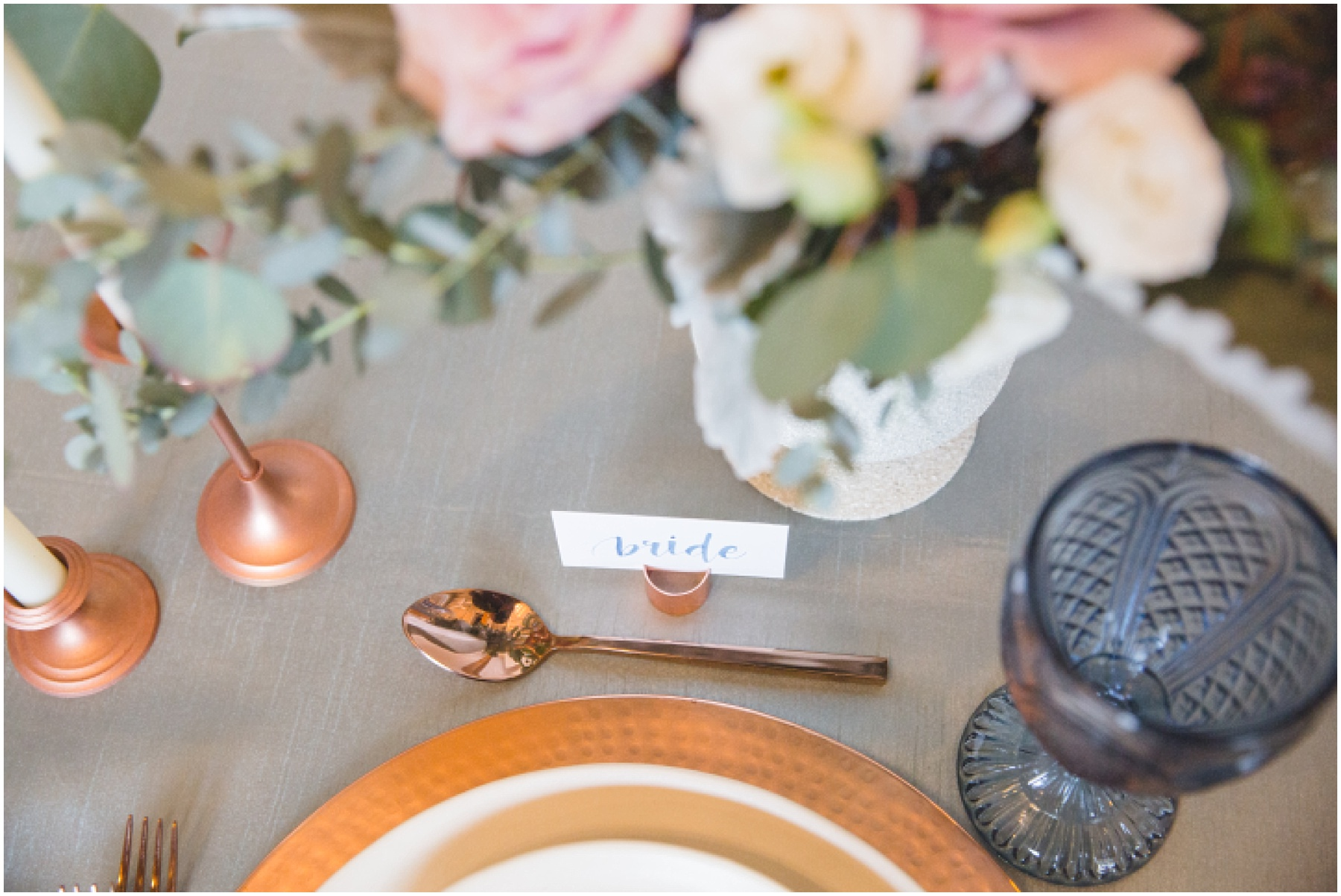 Styled wedding table scape with calligraphy place cards, rose gold accents, blue glass, and soft romantic florals by Social & Co Events.