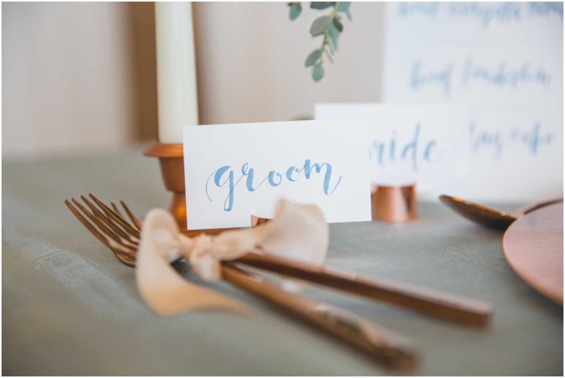 Styled wedding table scape details with blue calligraphy, rose gold cutlery, and white tapers