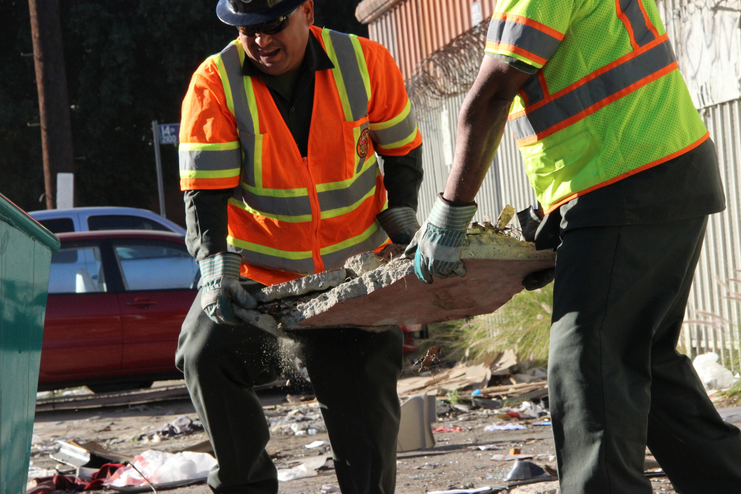 Clean Streets L.A. crew members remove construction waste and vehicle parts along with broken furniture and trash in an industrial area of Downtown Los Angeles. Every cleanup project of abandoned waste and illegal dumping presents challenges and hazards that are overcome.