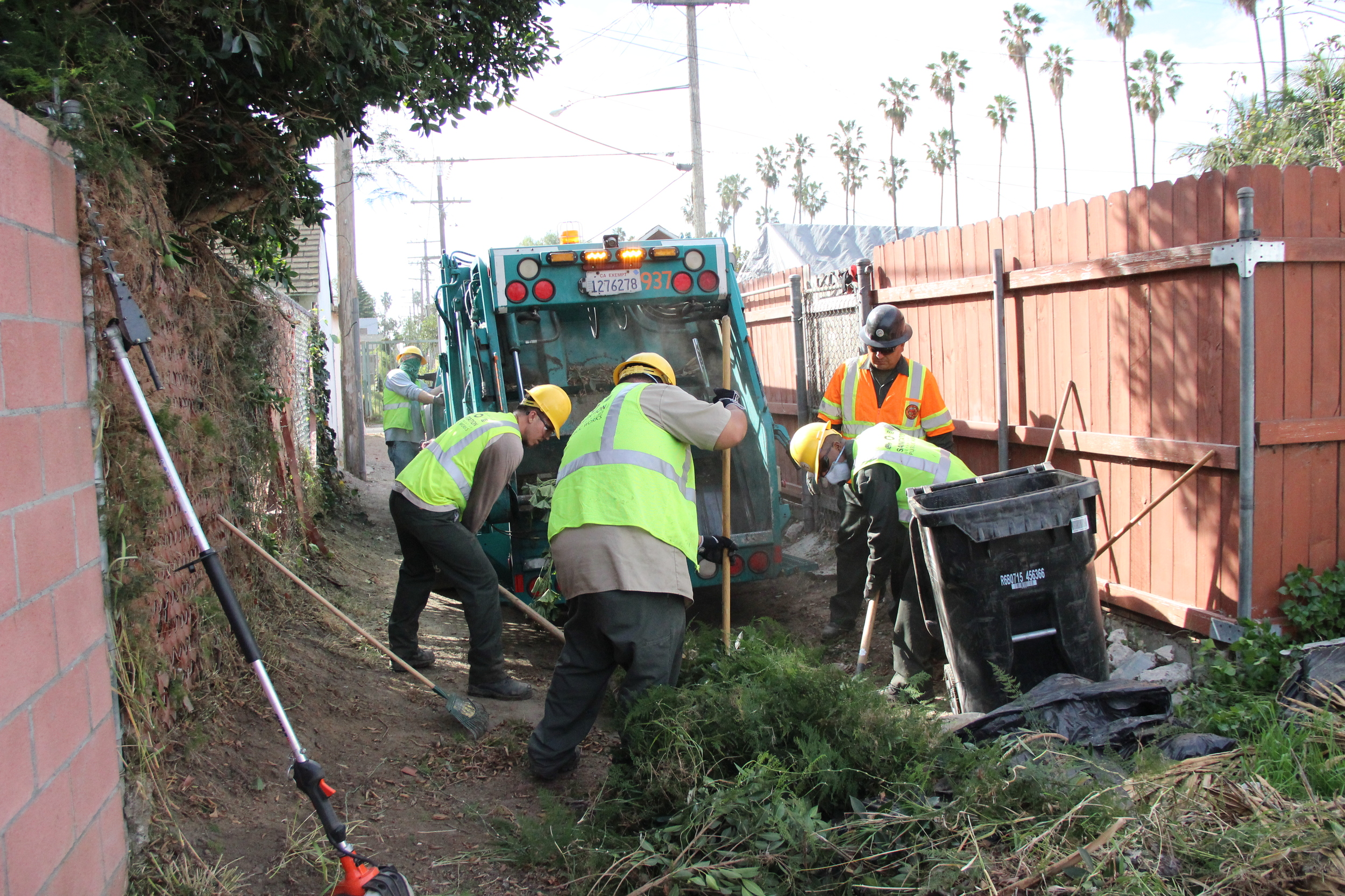 Clean Streets LA crew work five to ten feet at a time to remove vegetation in an alley more than a quarter mile long in Chesterfield Square.
