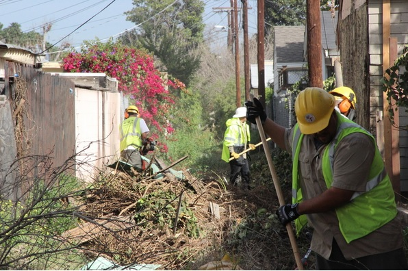 Clean Street L.A. crew in an alley with hand tools to cut and remove overgrown vegetation in Chesterfield Square South.