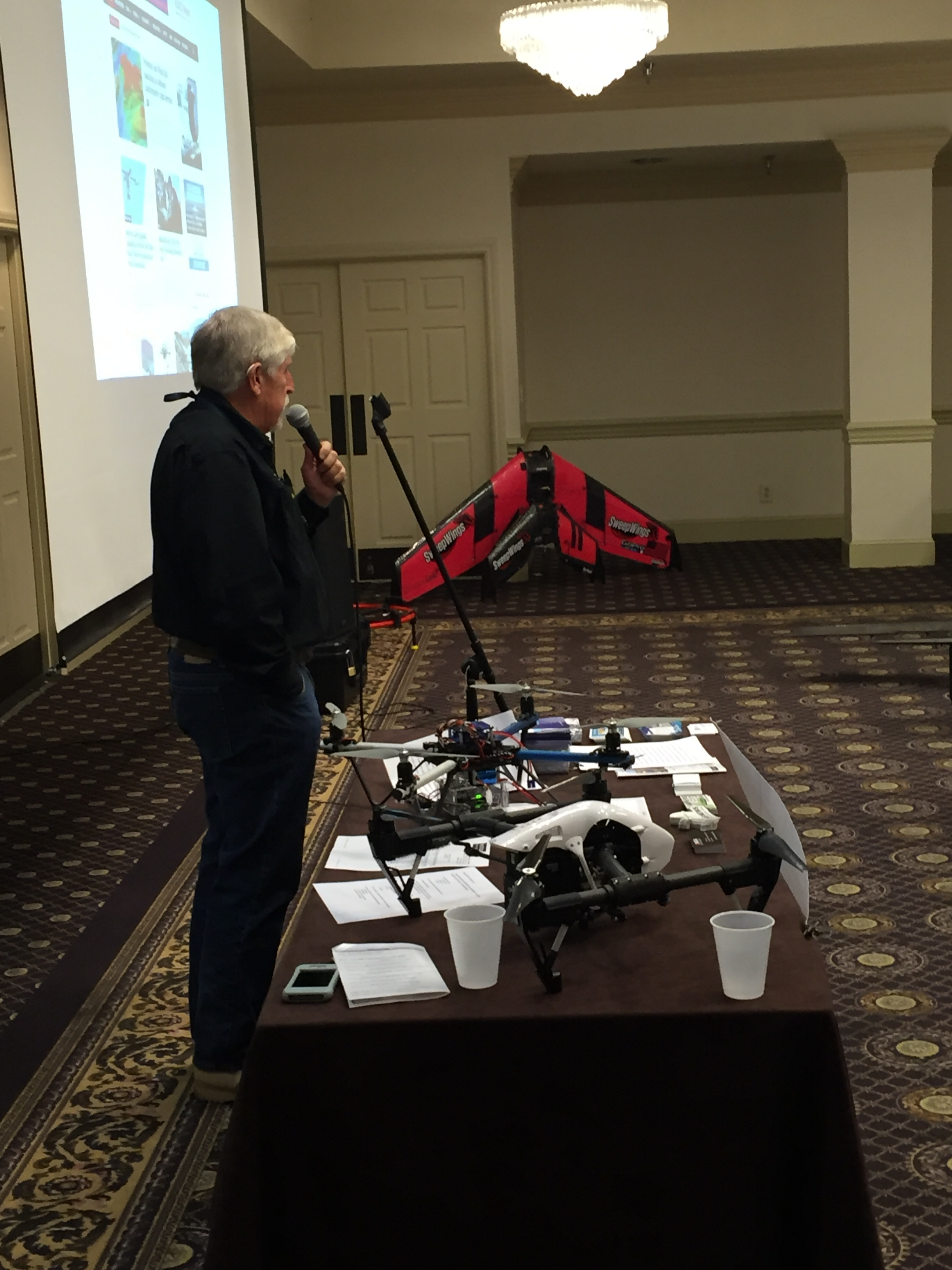 Bruce Parks, President of Drone Pilots Federation, provides an overview of the broad scopes and benefits of drone technology applications in our society. In the background are two flying wings that are designed, built, and flown by one of the other speakers at the event.