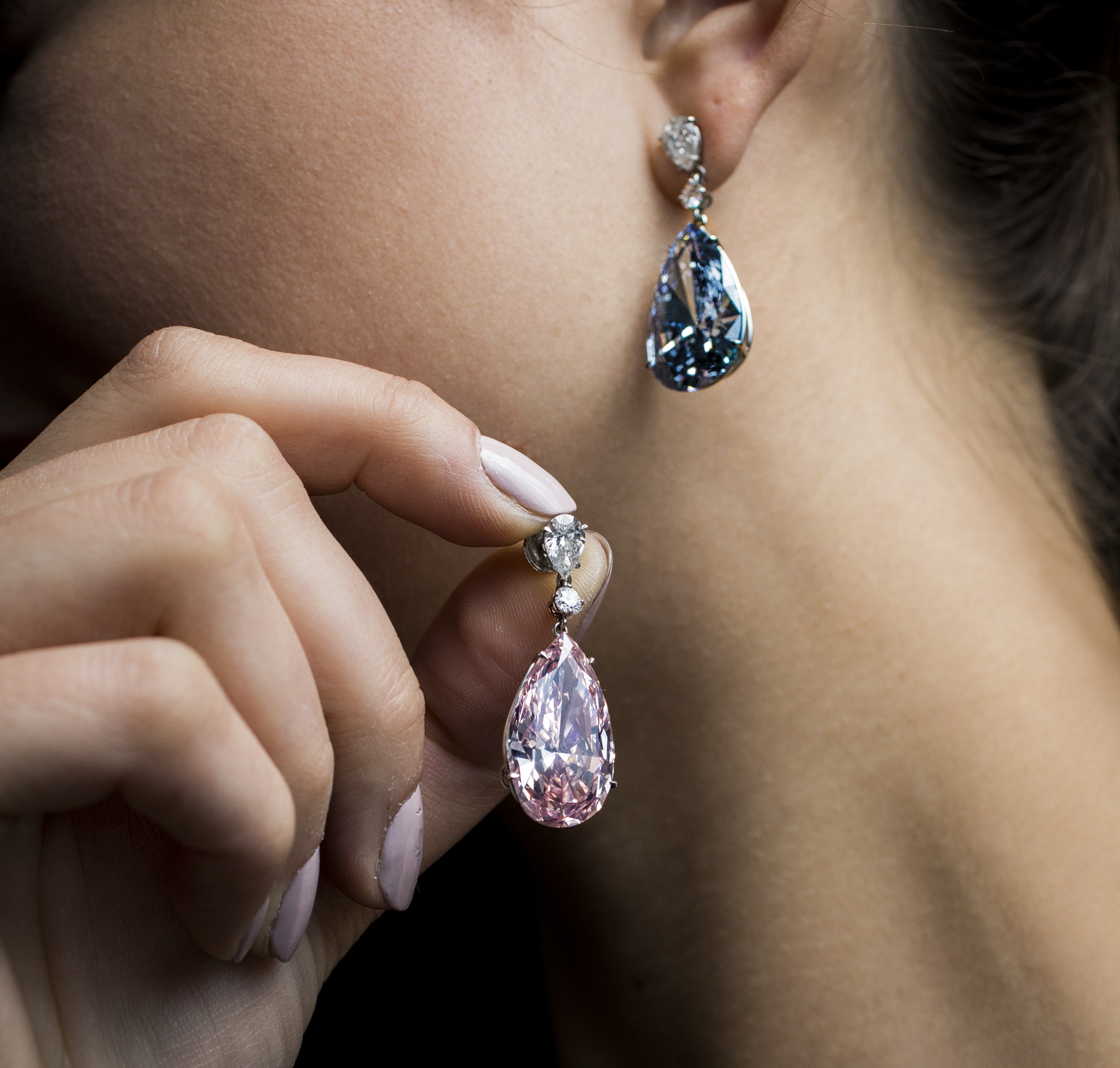 A Sotheby's employee displays the Apollo blue diamond and the Artemis pink diamond earrings during a preview at the Sotheby's, in Geneva, Switzerland. Sotheby's sold a pair of pear-shaped diamond earrings at a hammer price of about $51 million Tuesday, May 16, 2017, though the 14.54-carat flawless Fancy Vivid Blue diamond that was the auction's highlight fell short of the expected range.   Image courtesy of Sotheby's