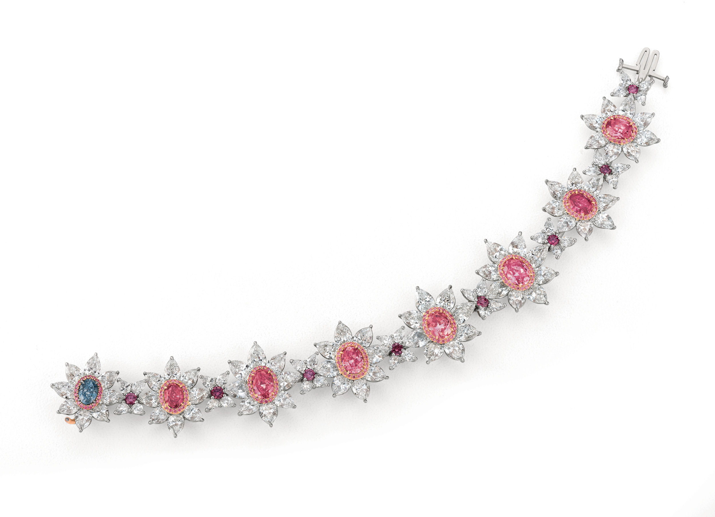 The Magnificent 8 Bracelet featuring 5 incredibly rare argyle intense to vivid purplish pink diamonds, 2 vivid pink diamonds and 1 vivid blue in a flower designer bracelet. Designed by Scott West