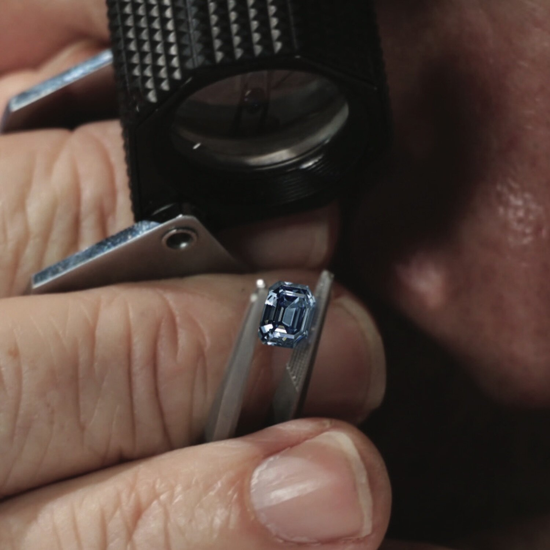 A gemologist studying a 3ct vivid blue diamond
