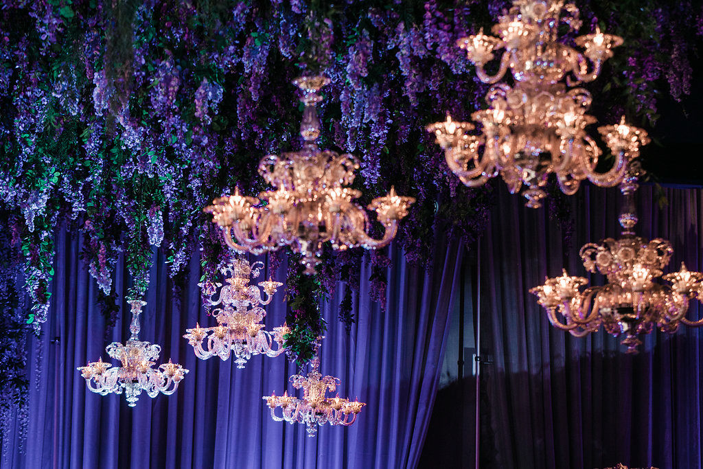 Chandeliers and purple wedding floral decor by Eddie Zaratsian Lifestyle and Design, Photo by Jessica Claire