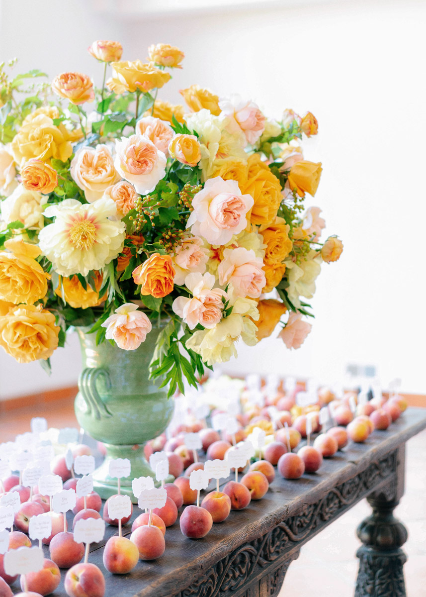 Peach seating card display at a summer garden wedding designed by Eddie Zaratsian