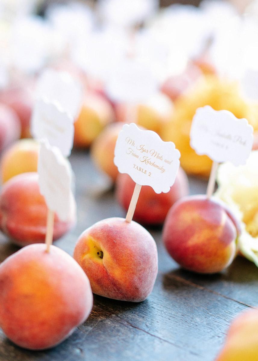 Fresh peach seating card display at a summer garden wedding designed by Eddie Zaratsian