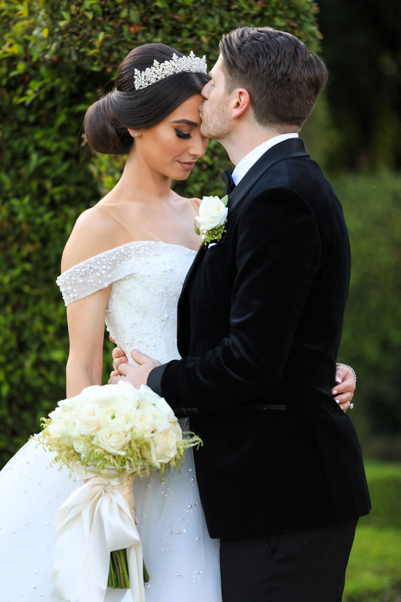 Glamorous, classic bride with a white bridal bouquet by Eddie Zaratsian and and groom in a velvet tuxedo