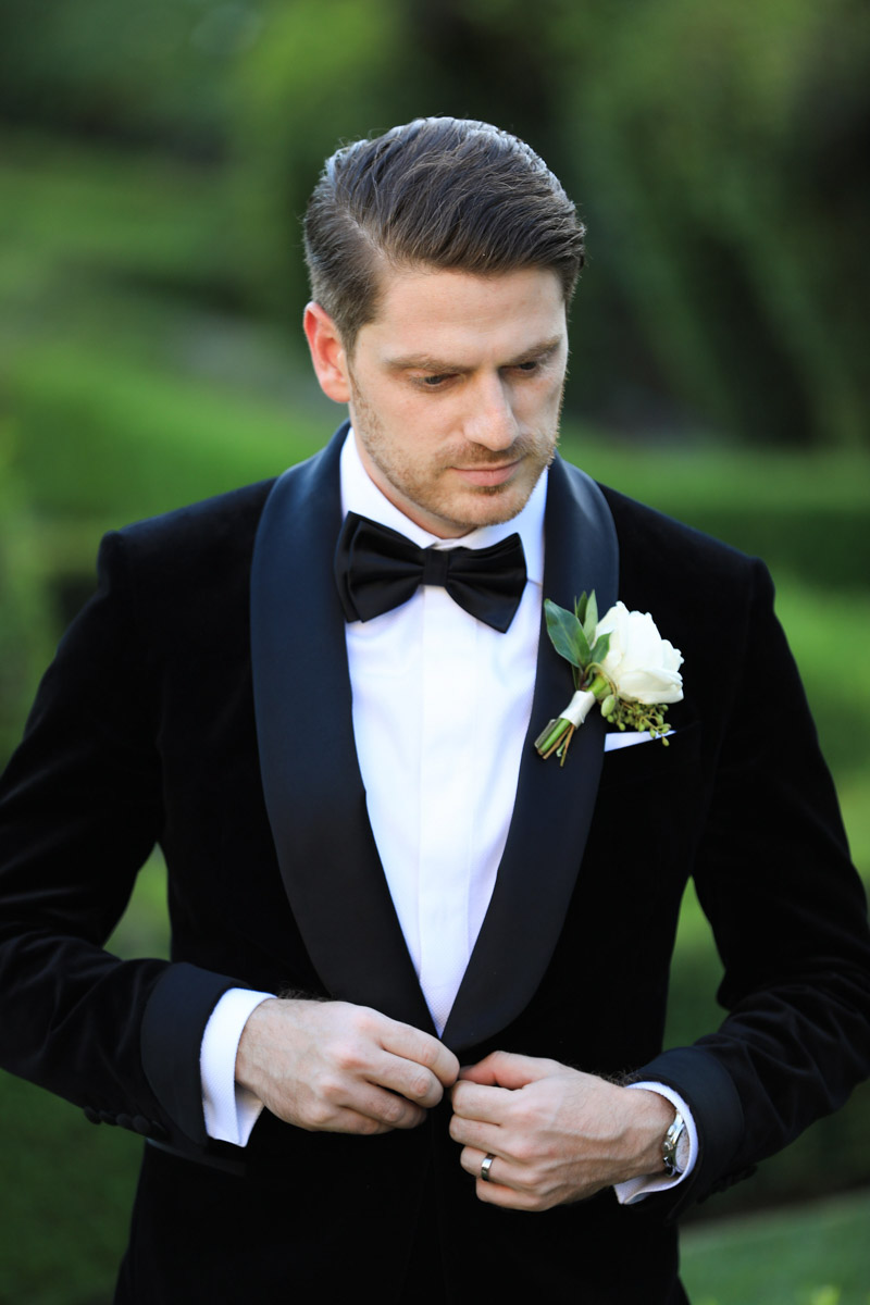 Classic groom in a velvet tuxedo with a white and green boutonniere by Eddie Zaratsian