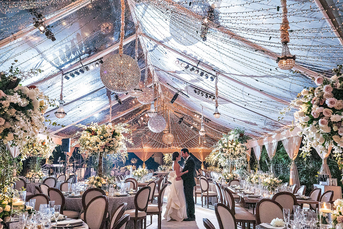 Hotel Bel-Air wedding reception tent with chandeliers and string lights, florals designed by Eddie Zaratsian, Photo by Jessica Claire Photography