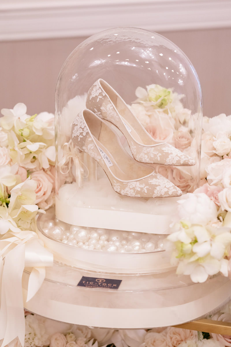 White lace Jimmy Choo bridal shoes under a glass dome, photo by Kris Kan