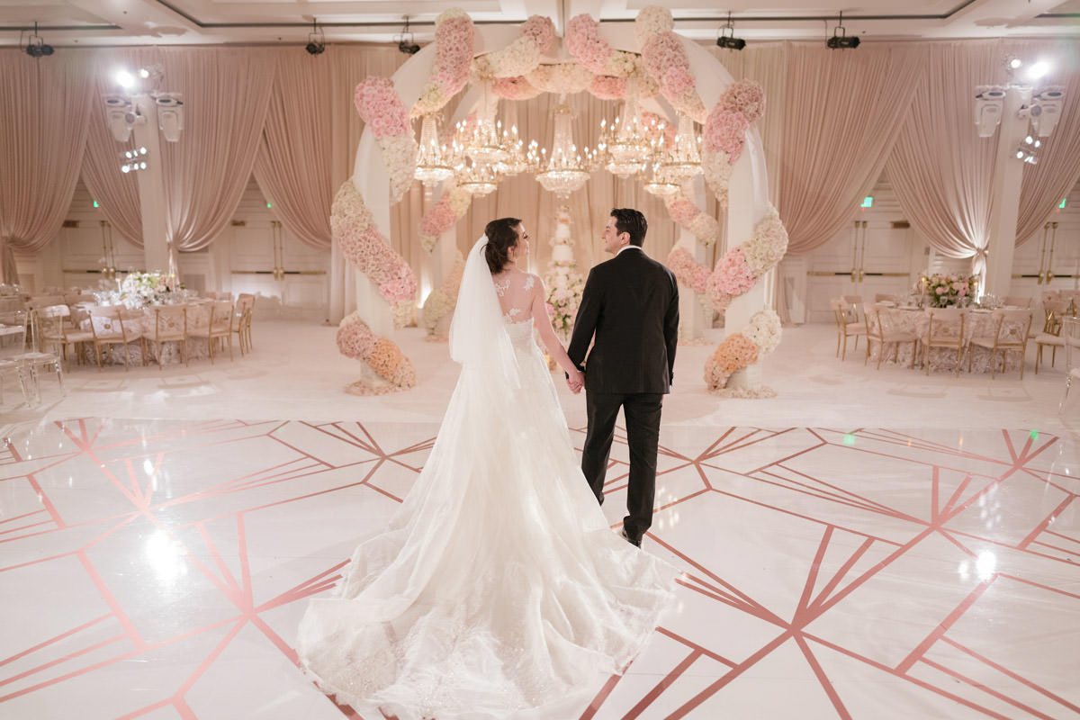 Bride and groom at their dramatic blush, cream and copper wedding reception, decor by Eddie Zaratsian, Photography by Kris Kan
