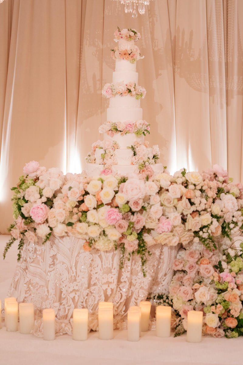 Wedding cake display overflowing with pink and white roses - florals designed by Eddie Zaratsian, photo by Kris Kan