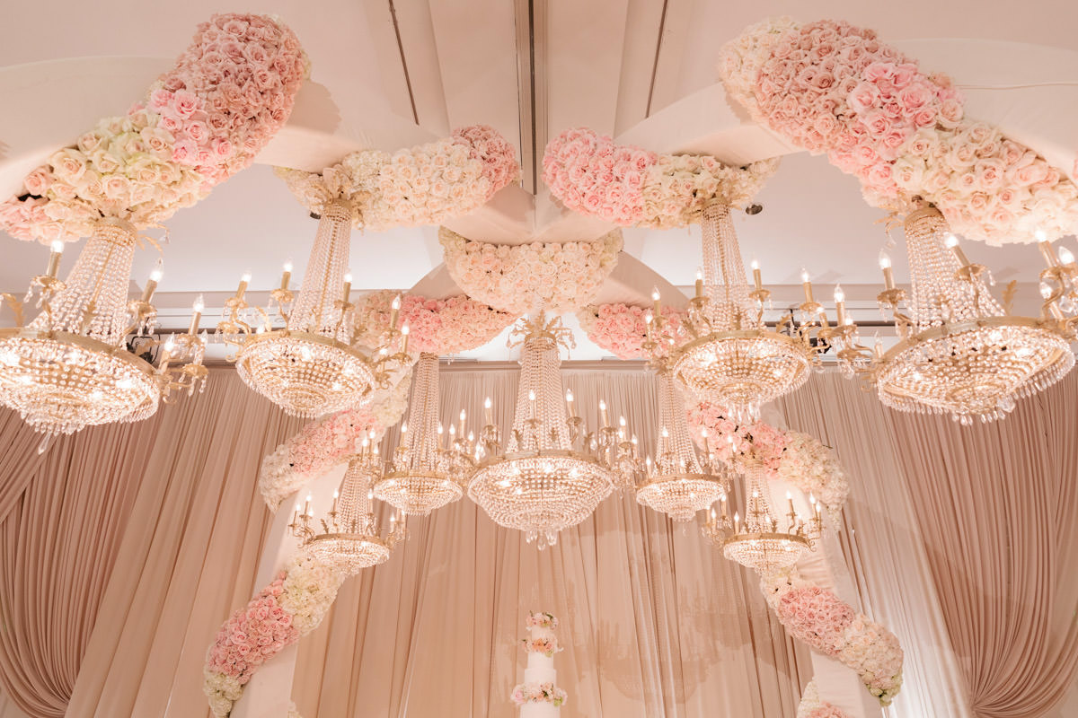 Incredible pink, cream and copper wedding reception floral arches, chandeliers and wedding cake table designed by Eddie Zaratsian, photo by Kris Kan