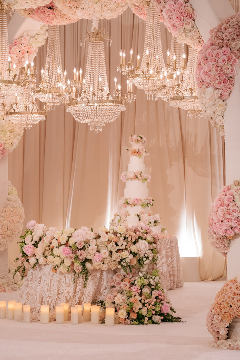 Wedding cake display and sweetheart table overflowing with pink and white roses, beneath sparkling chandeliers - designed by Eddie Zaratsian, photo by Kris Kan