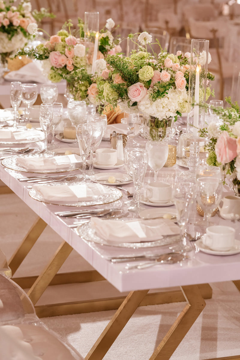 Wedding reception tables with translucent vases and candle holders and pink, white and copper accents - designed by Eddie Zaratsian, photo by Kris Kan