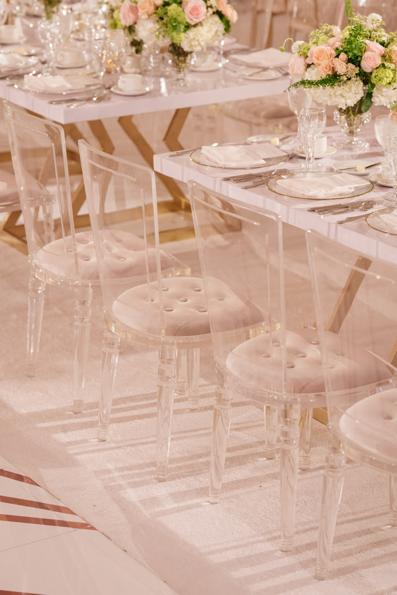 Wedding reception tables with translucent dining chairs and pink, white and copper accents - designed by Eddie Zaratsian, photo by Kris Kan