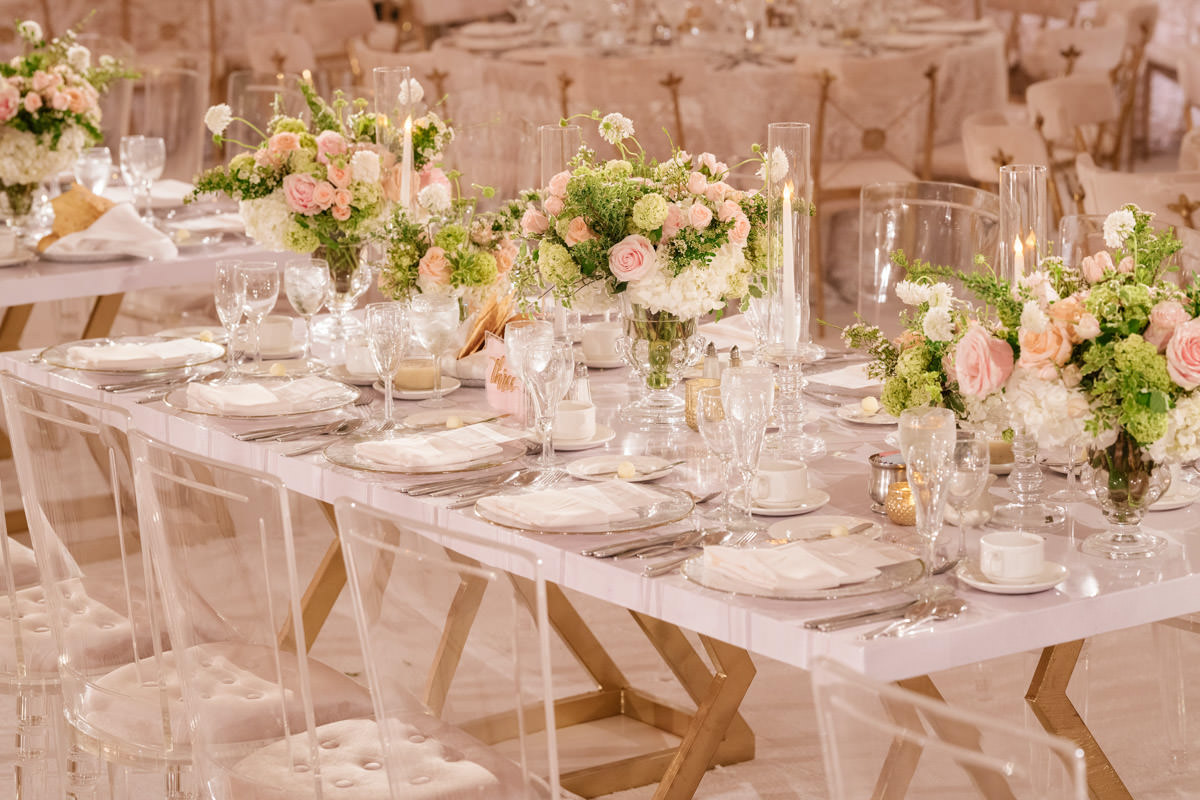 Wedding reception tables with translucent chairs, vases and candle holders, pink and white florals, and copper accents - designed by Eddie Zaratsian, photo by Kris Kan