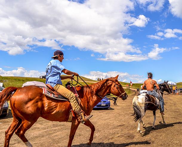 Two Standing Rock demonstrators take to horseback as part of the Standing Rock demonstrations that peaked in 2016. (Photo: Robert Wilson, via PRI)