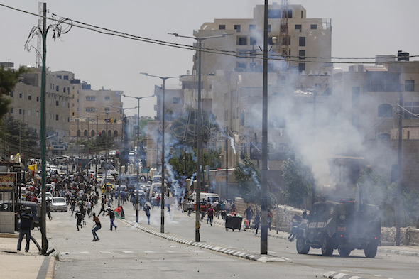 An Israeli security vehicle fires tear gas during clashes with Palestinians demonstrating in the West Bank city of Bethlehem in May. (Nasser Shiyoukhi / AP) via Truthdig