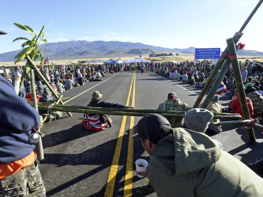 Demonstrators opposed to the construction of the Thirty Meter Telescope on Mauna Kea block access road. [Bruce Asato / Honolulu Star-Advertiser ]