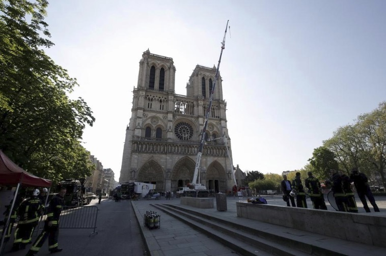A crane works at Notre-Dame cathedral in Paris, Friday, April 19, 2019. Rebuilding Notre Dame, the 800-year-old Paris cathedral devastated by fire last week, will cost billions of dollars as architects, historians and artisans work to preserve the medieval landmark.