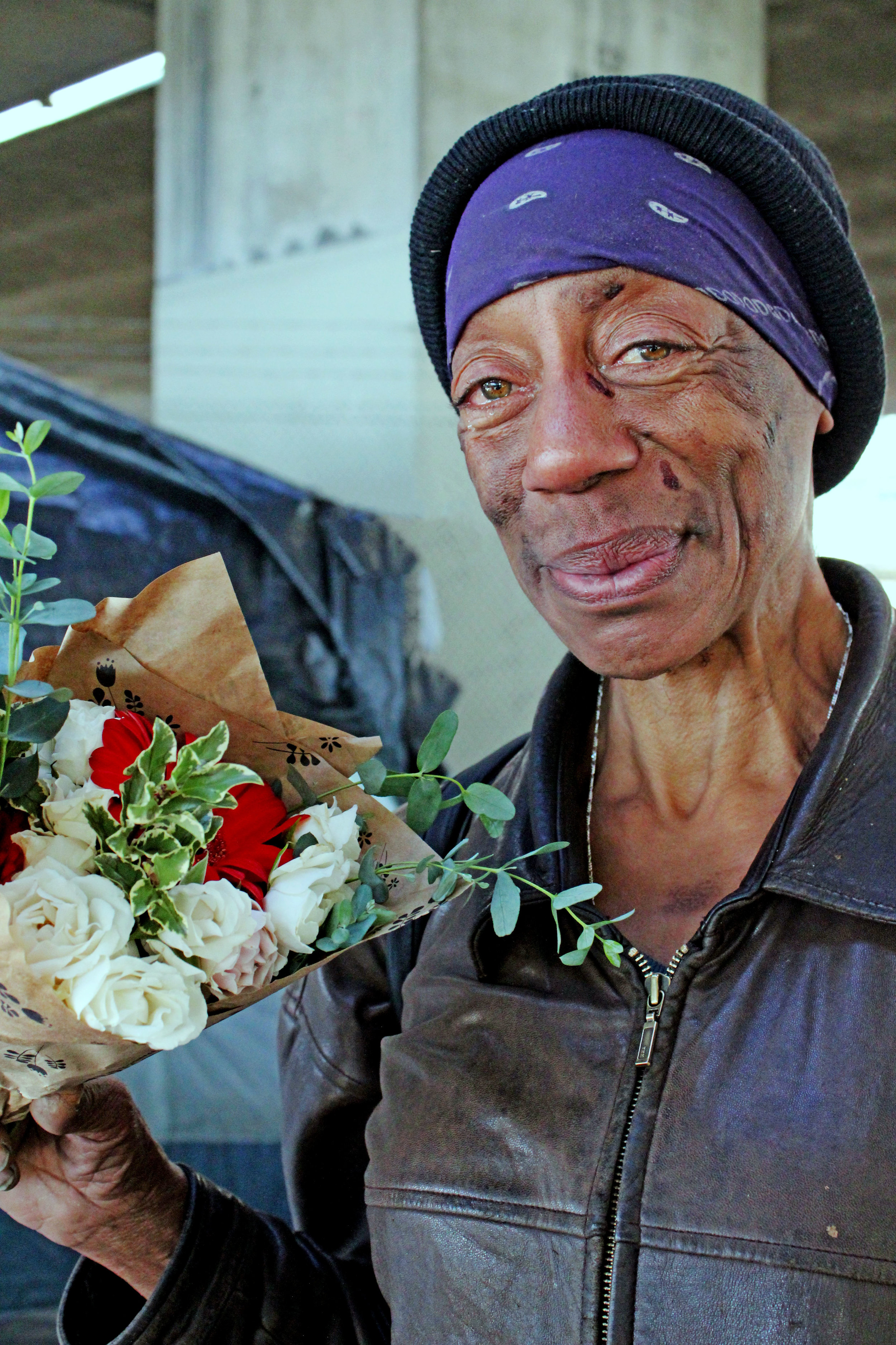 "Two weeks ago on Valentine's Day a group of activists and graffiti artists banded together to distribute tents and flowers to the Northgate homeless community in Oakland, CA. Evelyn, pictured here, is a Northgate resident who has been homeless for over 10 years. ""I had my own place, but my ex-husband stabbed me eight times, so I lost everything and I haven't been able to regroup,"" she says."