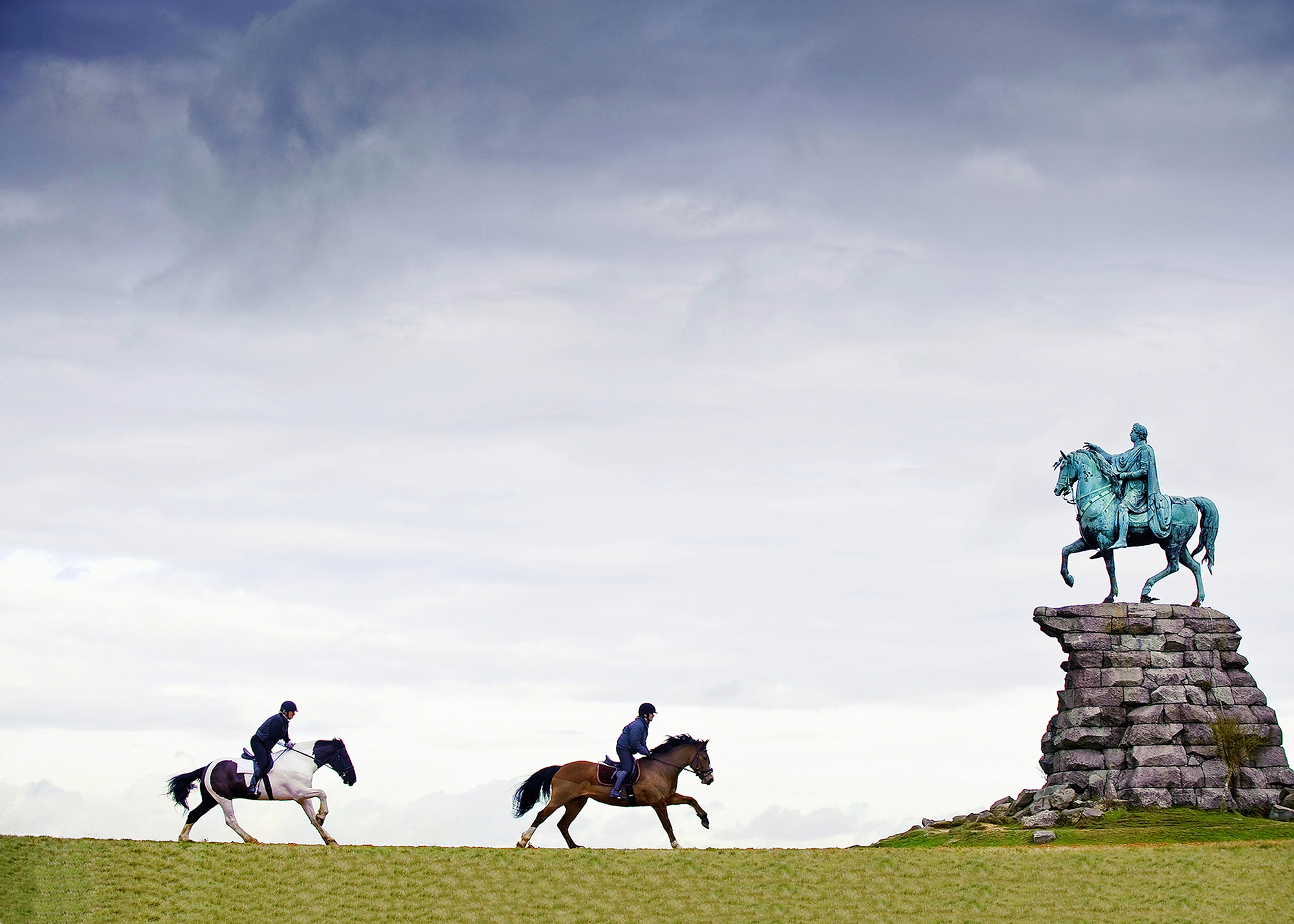 Rider gallops past the Copper Horse, a statue of King George III