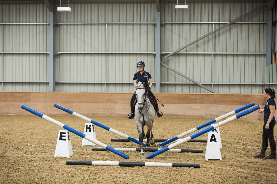 Raise the ends of the outside poles by about 2ft to give your horse the illusion that the channel is becoming narrower.