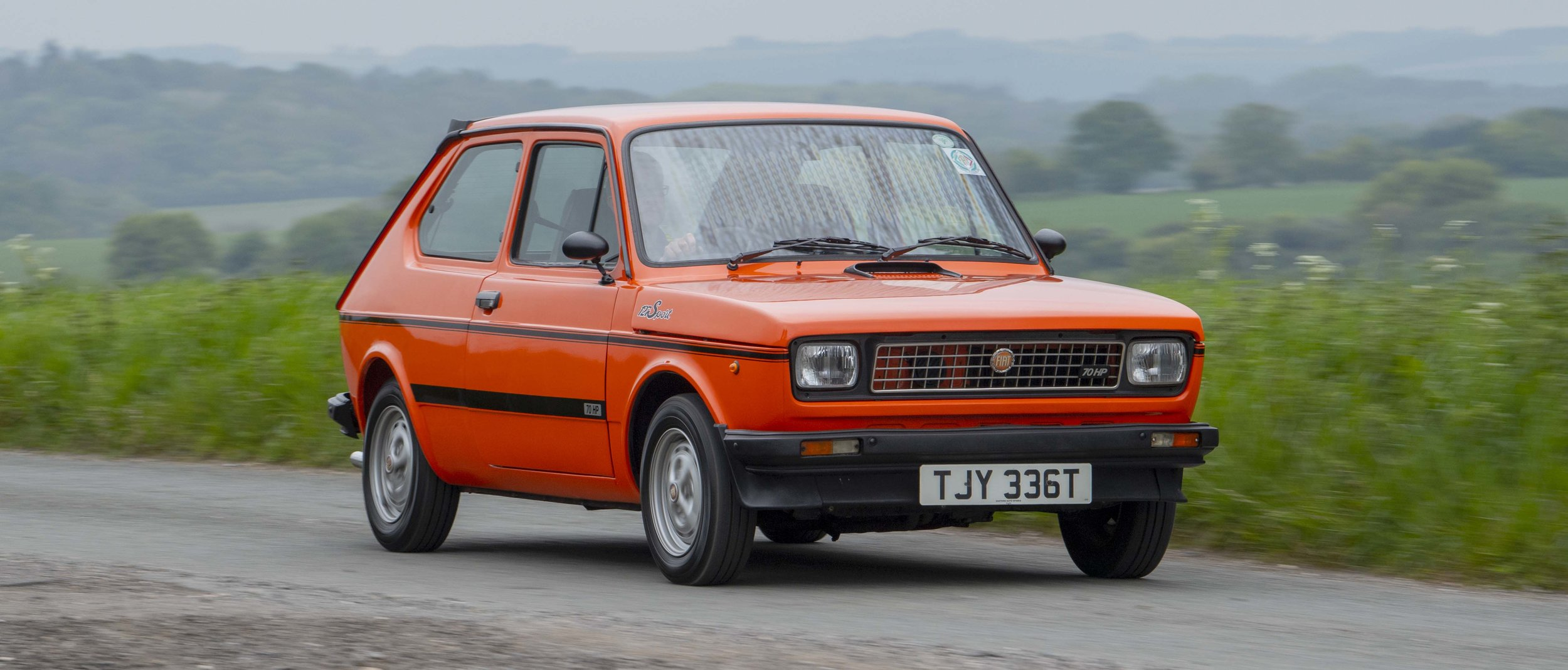 In 2018, Nigel Ford was watching a YouTube video that featured a couple of black Fiat 127s in the background. He got in touch with the guy who'd made it and was invited over to look at his orange Sport. It had been rebuilt and resprayed about ten years before but there was rust where it had been left unused and most of the wiring was unattached. It ran – barely - but was misfiring and stalling. The owner wanted £4000 for it and Nigel could see £1500 of work ahead of him. But he particularly wanted this car because it's a genuine Sport, which means it has various special parts including larger front brake discs, a stiffer and thicker anti-roll bar, wider wheels, re-profiled camshaft, bigger valves with increased compression ratio, Abarth twin exhaust and spoilers front and rear. The things we do for love…