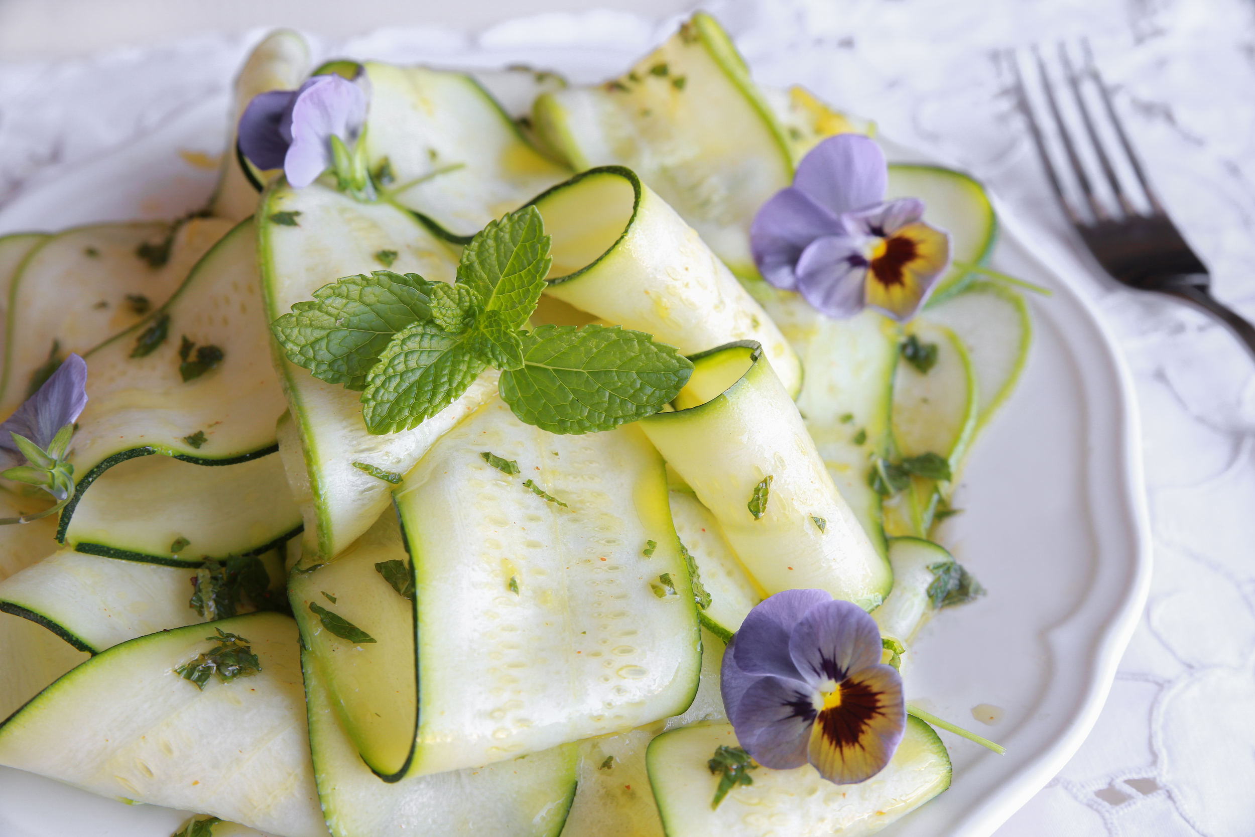 Add pansy petals to sliced courgette and garnish with mint