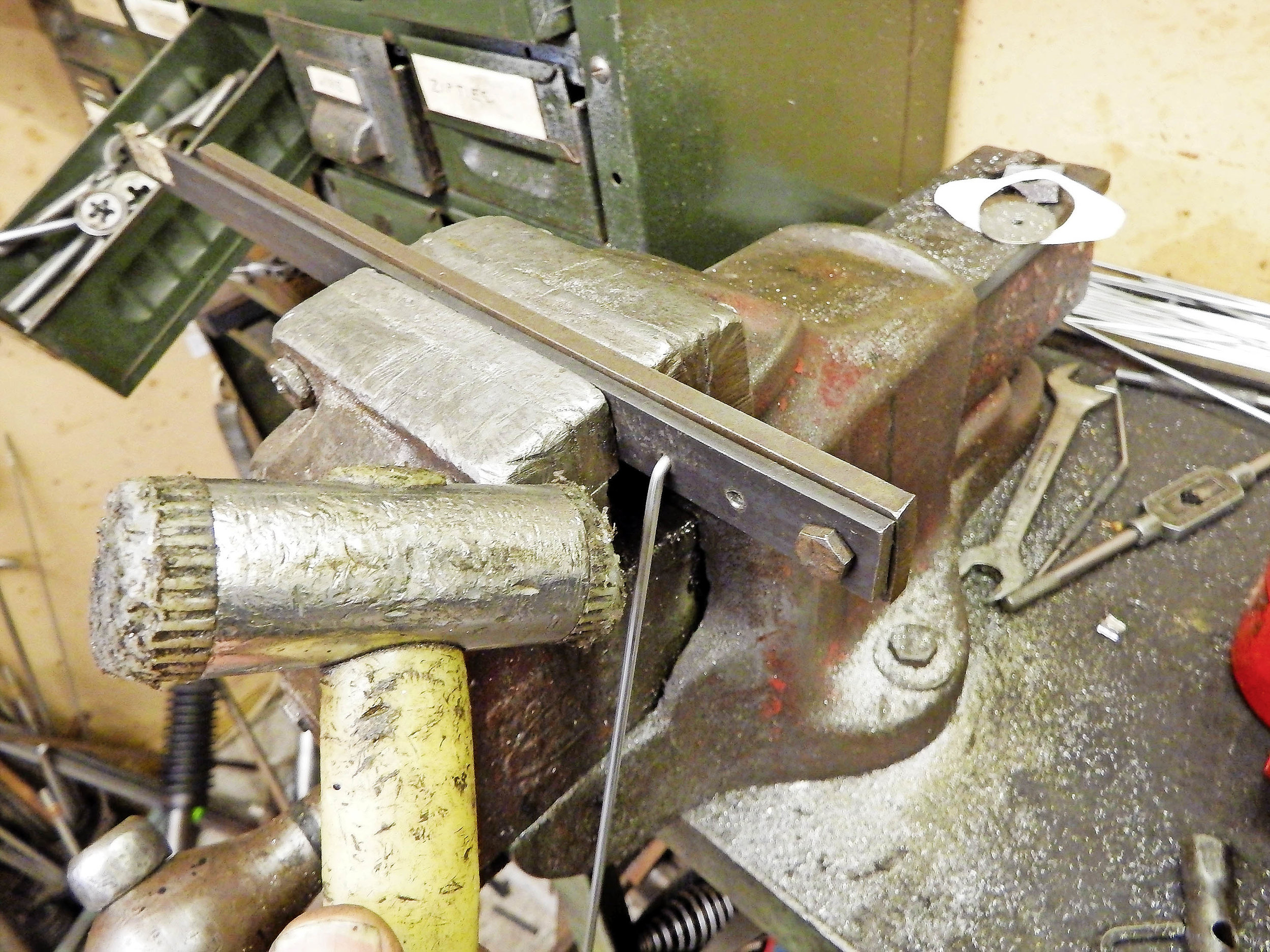 2.  Insert the spoke into the jig, close it and tighten it in the bench vice. With the head gripped securely, you can now use a soft hammer to bend the spoke to the desired angle.