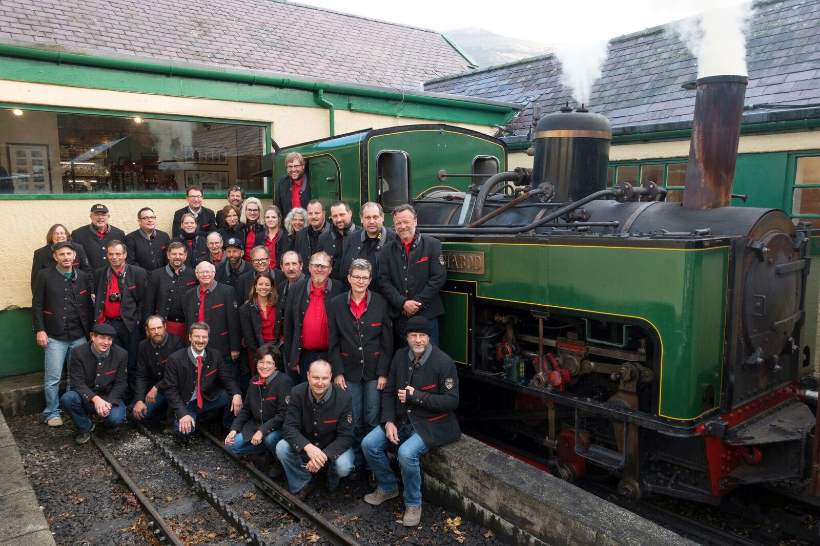 The Brienz Rothorn Bahn staff gather in front of newly overhauled SMR No. 5  Moel Siabod  at Llanberis station. SMR